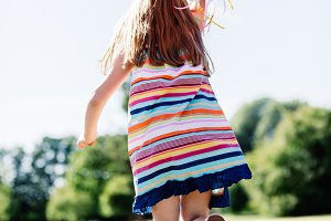 Little girl in a striped dress holding balloon strings