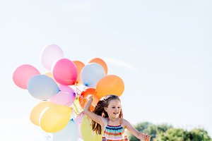 Young girl in a dress running with a bunch of balloons.
