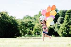 Young girl running on the grass field with balloons.