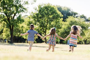 Three little children running on a green field
