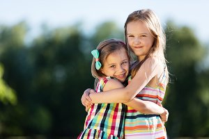 Two little girls hugging each other in the park.