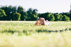 Little girl laying on the grass field and looking aside.