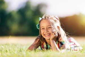 Little smiling girl laying on the grass field in the park.