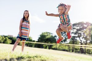 Little girl in a colorful dress jumping through the elastic.