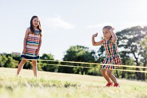 Two girls playing Chinese jumping rope in the park.