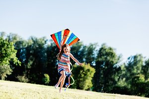 Happy little girl holding a kite and running
