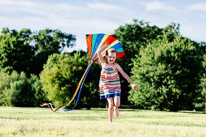 Happy girl running on the grass field with a colorful kite.