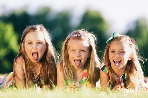 Three little girls sticking their tongues out