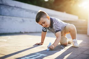 Little boy drawing with a chalk on a concrete pavement.