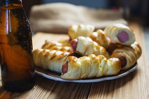 Sausages in the dough on a wooden table for beer