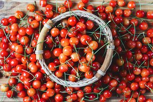 Basket with ripe fresh sweet cherry on a wooden table