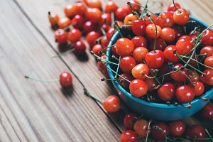 Fresh cherry in a bowl on a wooden table
