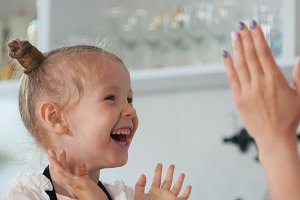 Happy little girl with her mother clap their hands in the kitchen