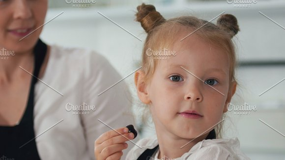 Portreat of a cheerful little girl licks a berry and looking at the camera