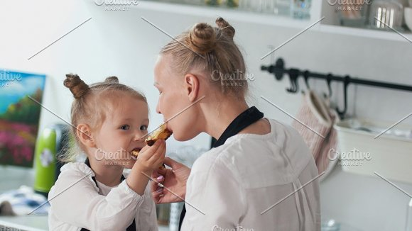 Cheerful little girl with her mother feed each other homemade pancakes