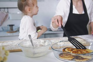 Cute mom with her little daughter cooking cottage cheese pancakes