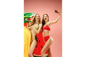 Cute girls in swimsuits posing at studio. Summer portrait caucasian teenagers on pink background.