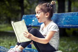 little girl is sitting on a bench and is reading a book