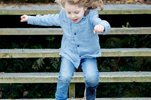 Child jumping a wooden stairs