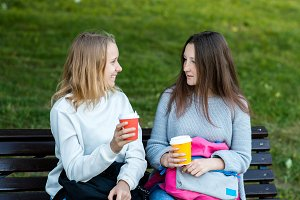 Two girl friends. In the summer on bench. They talk with hands holding cups of coffee and tea. A schoolgirl is resting after classes in the city. Smiles happily.