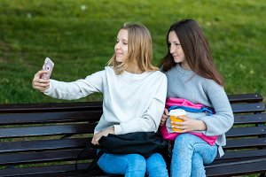 Two little girls are schoolgirls. In summer on the bench. Hands holding phone. Photographs on a smartphone. In the summer after school. The concept of the best girlfriends. Emotion is a pleasure.