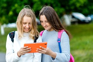 Two girl friends schoolgirl. Summer in nature. In her hands holds a tablet. Behind the backpack. The concept of watching videos on social networks. Emotions and smiling happily.