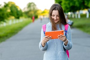 Girl schoolgirl. Summer in nature. Hands holding a tablet behind his backpack. Free space for text. The concept of watching videos from Internet. Emotion happy enjoys listening to music.
