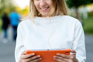 Girl schoolgirl teenager. Summer in nature. Hands holding a tablet. The concept of watching videos from social networks. Emotion happy enjoys listening to music on Internet.