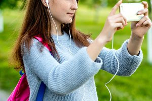 Beautiful schoolgirl girl teenager. Summer in nature. In his hands holds a smartphone behind his backpack. Photographs on phone. Play music on headphones. Emotion smiles happily.