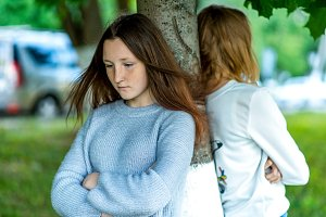 Two girls in summer in the park. The concept of school friends in a quarrel, a problem teenager. Emotions of conflict, discontent, resentment, frustration, anger. 2 sisters on street in the city.