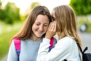 Two girl friends schoolgirls teenagers. In summer city park. Concept of joke, secret, fantasy, conversation, whisper, surprise. Emotion of happiness is pleasure, joy, smile, pleasure.