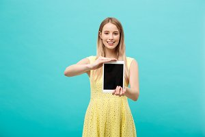 Pretty smiling woman showing blank black screen of digital tablet. Isolated over blue background.