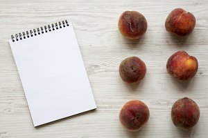 Fresh peaches with notepad on white