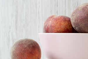 Pink bowl of ripe peaches on white