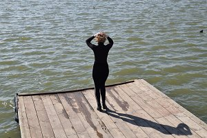 A girl with a beautiful figure in black tight clothes on a wooden pier by the pond