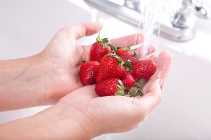 Woman Washing Strawberries in the Kitchen Sink.