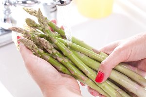Woman Washing Asparagus in the Kitchen Sink.
