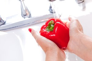 Woman Washing Red Bell Pepper in the Kitchen Sink.