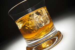 Glass of Whiskey or Other Alcoholic Drink and Ice Under Spot Light.