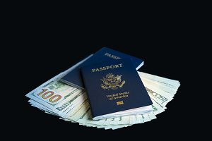 Two USA passports on a pile of dollar bills for travel concept