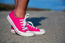 Pink sneakers on young woman legs