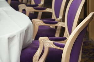Several Luxurious Purple Chairs Lined Up in a Formal Dining Room.