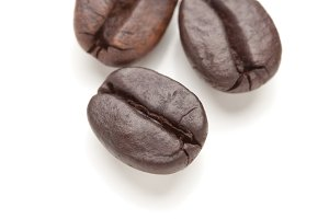 Three Roasted Coffee Beans Isolated on White with Narrow Depth of Field.