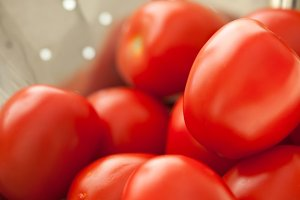 Macro of Fresh, Vibrant Roma Tomatoes in Metal Colander Abstract.