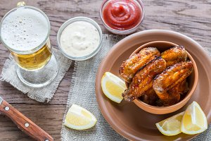 Caramelized chicken wings with glass