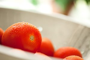 Macro of Fresh, Vibrant Roma Tomatoes in Colander with Water Drops Abstract.