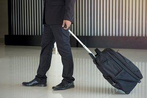 man drag luggage walk to hotel