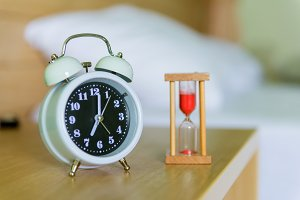 alarm clock with hourglass on bed