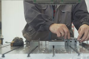 Worker with a scraper chamfering removing burrs on metal object for manufacturing industrial CNC machines
