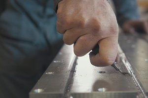 Male hands makes chamfering removing burrs on metal panel with a scraper